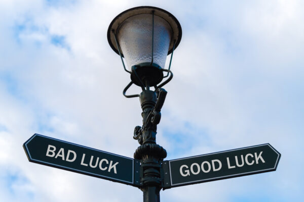 Street lighting pole with two opposite directional arrows over blue cloudy background. Bad Luck versus Good Luck concept.